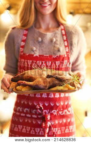 Roast duck and potato on wooden plate in womans hands. Christmas dinner