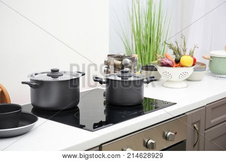 Cooking utensils on electric stove in kitchen