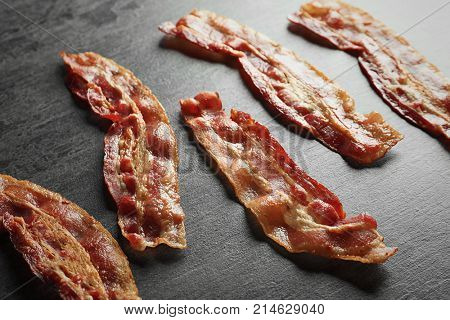 Cooked bacon rashers on wooden table, closeup