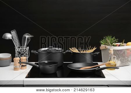 Different cooking utensils on electric stove against black background