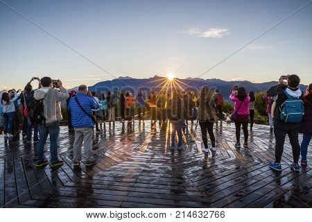 Alishan Taiwan - November 8, 2017: Tourists in unison photograph sunrise appear over edge of Zhushan mountain at Alishan recreation area of Taiwan.
