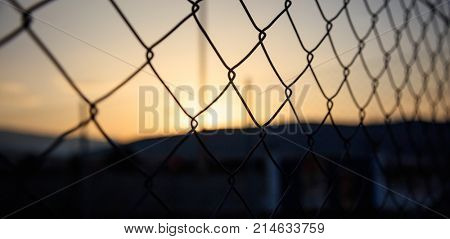 Steel wire mesh fence on a sunset background. Blurred smokestacks and mountains silhouette.