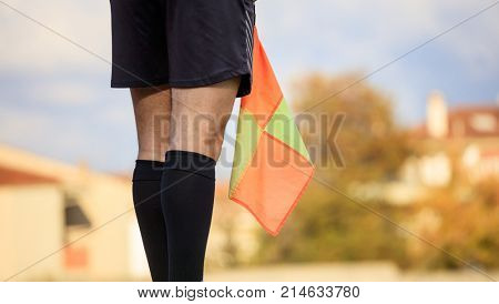 Football assistant referee on the field standing and holding the flag. Blurred background.