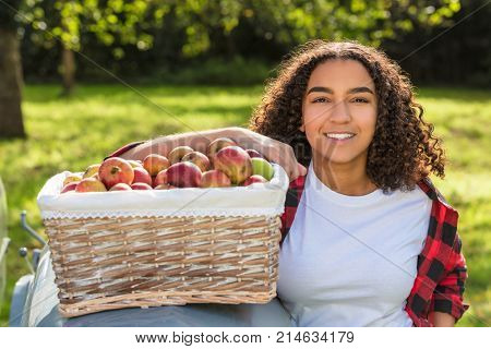 Beautiful happy  girl teenager female young woman smiling with perfect teeth in an orchard resting on a tractor with baskets of organic apples she has been picking