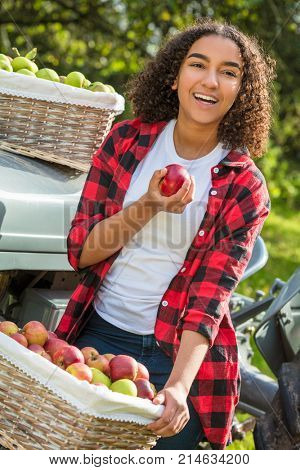 Happy girl teenager female young woman smiling with perfect teeth in an orchard resting on tractor eating an apple with baskets of organic apples she has been picking