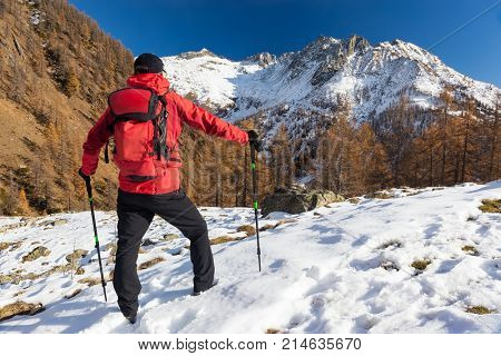Man is backpacking in winter mountains. Piemonte, Italian Alps, Europe. Concepts: vacation, adventure, hiking, enterprise, self realization.
