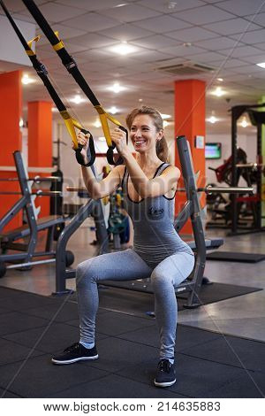 Closeup of attractive fit sportswoman working out in functional training at gym, doing exercise with ropes