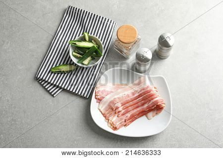 Plate with rashers of bacon on table