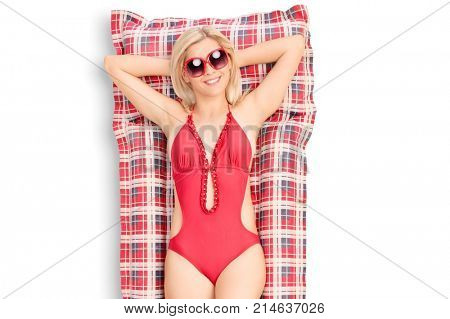 Beautiful young woman in a red swimming suit lying on an air matress isolated on white background