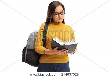 Female teen student with a backpack reading a book isolated on white background