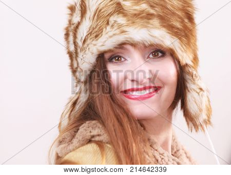 Winter fashion. Young smiling woman wearing fashionable wintertime clothes fur cap studio shot on gray