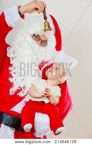 Christmas time people concept. Santaclaus with little baby. Man has red outfit and child is hugging him.