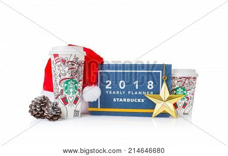 Chiang Mai Thailand- 18 November 2017 - 2 sizes Grande and Venti of Starbucks Coffee paper cups in beautiful 2018 Christmas design set up on display with holiday special design notebook on white background in Chiang Mai Thailand on November 18 2017