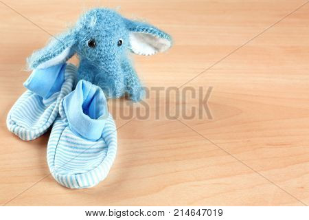 Baby's first bootees with toy on wooden table