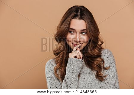 Cute shy woman in woolen jersey looking aside, isolated on beige background
