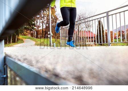 Unrecognizable young athlete in yellow jacket running outside by the lake. Trail runner training for cross country running in colorful sunny autumn nature.