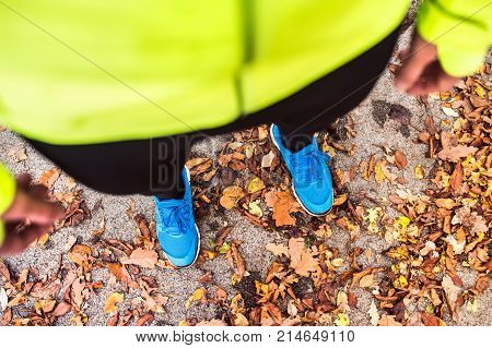 Unrecognizable young runner in yellow jacket outside in colorful sunny autumn nature standing on an asphalt path. Trail runner training for cross country running.
