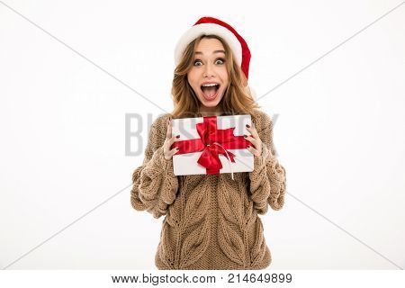 Shocked young woman dressed in warm sweater wearing christmas hat standing isolated over white wall background. Looking camera holding gift box surprise.