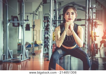 Young Asian Woman Doing Squat Workout For Fat Burning And Diet In Fitness Sports Gym With Sports Equ