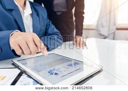 Investor executive pointing growth by graph and discussing plan financial graph data my team at office. Business team recheck summary or annual audit of financial information. Business team meeting.