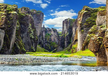 Magic beauty canyon in Iceland - Fyadrarglyufur. Steep cliffs, overgrown with green moss, surrounded by very fast river with cold water
