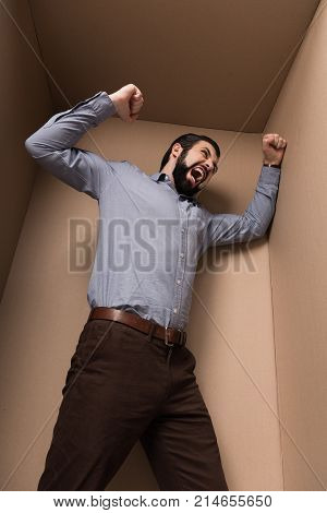 young angry man yelling in cardboard box
