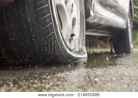 Car flat tire on street in rainy day