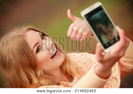 Nature outdoor internet technology concept. Cheerful blonde girl taking selfie. Young gorgeous lady takes picture of herself in autumnal forest.