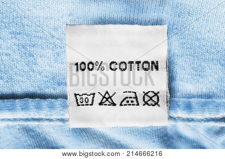Fabric composition and washing instructions clothes label on blue cotton closeup