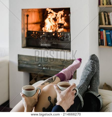 Feet in woollen. Pair relax with a cup of hot drink and warming up their feet in woollen socks. Close up on feet. Winter and Christmas holidays concept.