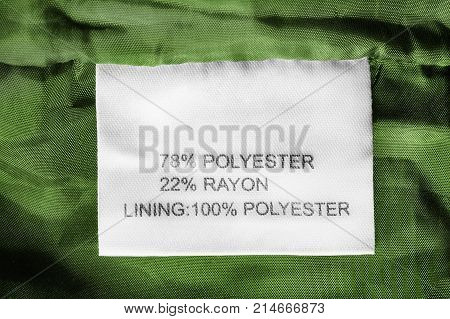 Fabric composition clothes label on green textile background closeup