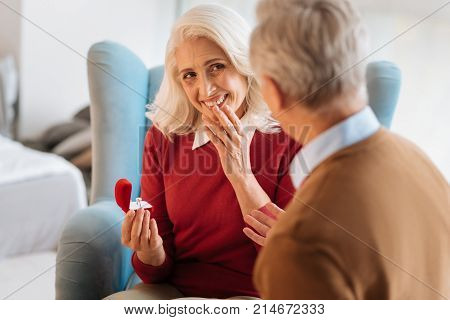 Will you marry me. Selective focus on a pretty senior woman looking at his soulmate with eyes full of love while holding a ring in a red velvet box and listening to his proposal.