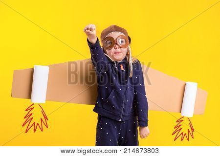 Freedom, girl playing to be airplane pilot, funny little girl with aviator cap and glasses, carries wings made of brown cardboard as an airplane. Studio photography on a yellow background