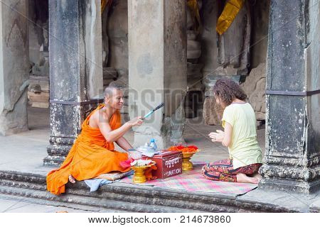 Siem Reap, Cambodia - Dec 05 2016: Buddhist Monk Give A Wish To People In Angkor Wat. A Famous Histo