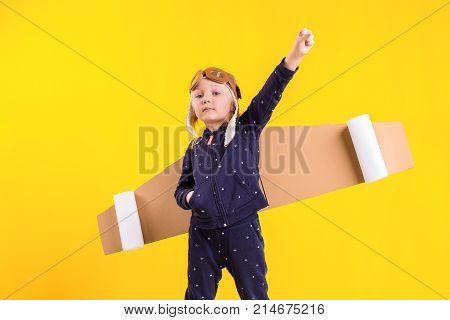 Freedom, girl playing to be airplane pilot, funny little girl with aviator cap and glasses, carries wings made of brown cardboard as an airplane. Studio photography on a yellow background. Imagination or exploration concept