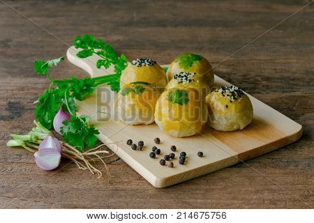 Chinese pastry or moon cake filled with mung bean paste and salted egg yolk decorate with coriander and sesame. Delicious Chinese pastry and some ingredients on wood table in side view, copy space. Homemade bakery concept of Chinese pastry or moon cake.