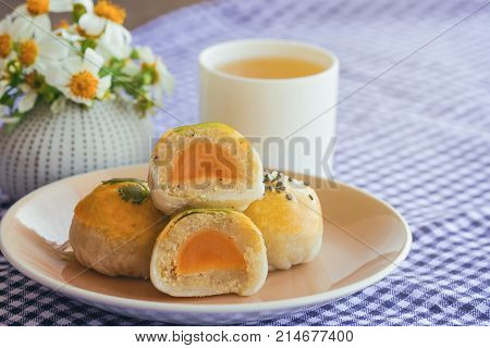 Chinese pastry or moon cake filled with mung bean paste and salted egg yolk. Delicious Chinese pastry on wood basket served with tea on wood table in side view close up with copy space. Homemade bakery concept of Chinese pastry or moon cake.