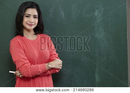 malay woman or teacher holding white chalk looking at camera with smile