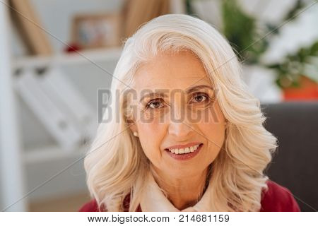 Unearthly beauty. Charming senior lady on heavenly beauty wearing earrings with pearls looking into the camera with a cheerful smile on her face while enjoying a day spent at home.