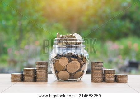 Coins in jar with money stack step growing money Concept finance business and saving investment.
