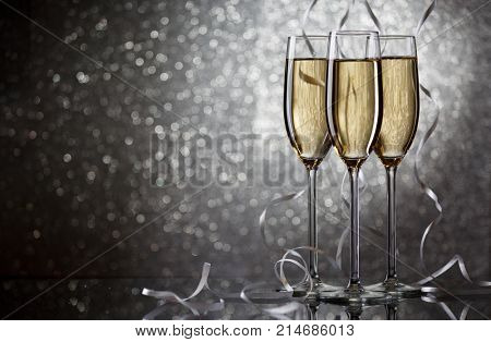 New Year's picture of three wine glasses with sparkling champagne with white ribbons