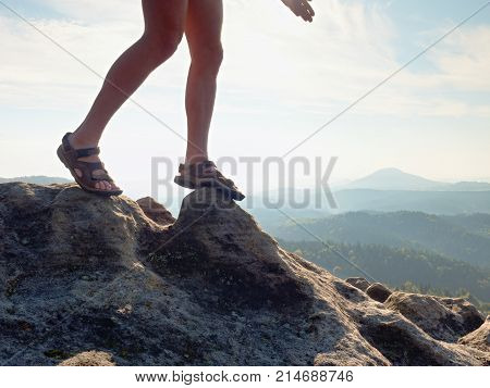 Long Tired Naked Legs In Hiking Sandals On Peak. Hiking In Sandstone Rocks, Hilly Landscape