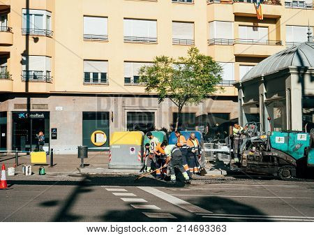 BARCELONA SPAIN - NOV 12 2017: Team of workers posing asphalt on the street of Barcelona on the Via Augusta street ona warm autumn day