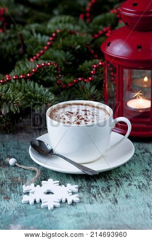 A cup of fragrant coffee on a wooden background. Coffee cappuccino with Christmas spruce branches and ornaments on an old wooden background. Christmas background Coffee Cocoa Cappuccino Coffee cup Wooden background