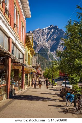 BANFF, ALBERTA, CANADA - JUNE 27, 2017 : Scenic street view of the Banff main shopping street in a sunny summer day. Banff is a resort town and popular tourist destination.