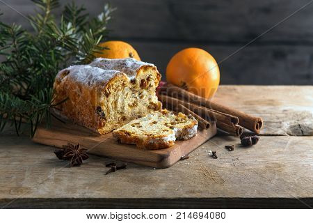 Christmas cake in germany christstollen with fir branches oranges cinnamon and anise stars on a rustic table wooden vintage background with copy space selected focus very narrow depth of field