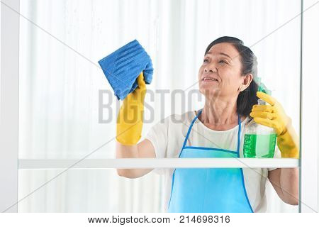 Senior Vietnamese woman cleaning window with special spray
