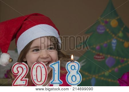 Pretty little girl blowing out candles - closeup shot. background of a painted Christmas tree