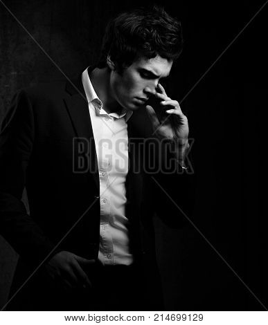 Thinking Charismatic Man Posing And Looking Down On Dark Shadow Dramatic Light Background. Closeup P