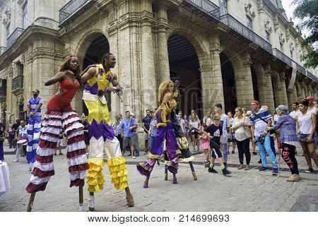 HAVANA, CUBA - 16 FEB, 2017: Colorful parade of stilt dancers in Old Havana street, the performers use public spaces like squares to interact with tourists and locals.